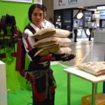 Student lifts bags of rice with University of Tokyo's bionic suit at CEATEC 2012.