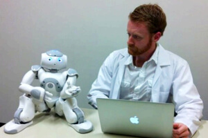 Nao robot sitting beside a human researcher.