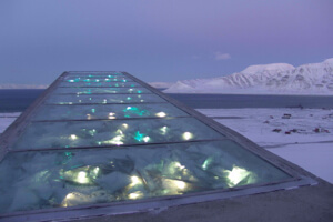 The doomsday vault's entrance is a patchwork of reflective steel, mirror glass, and prisms lit by the arctic sun in summer and fiber optics in winter.