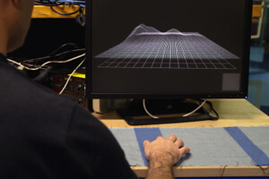 A screen displays touches registered on a section of conductive fabric.