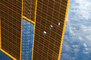 Three tiny CubeSats drift alongside the ISS solar arrays. (Image Credit: NASA)
