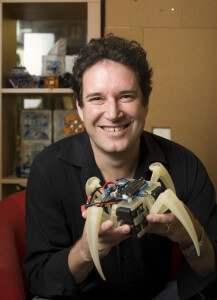 Hod Lipson, associate professor of mechanical and aerospace engineering, in his Upson Hall with a robot.