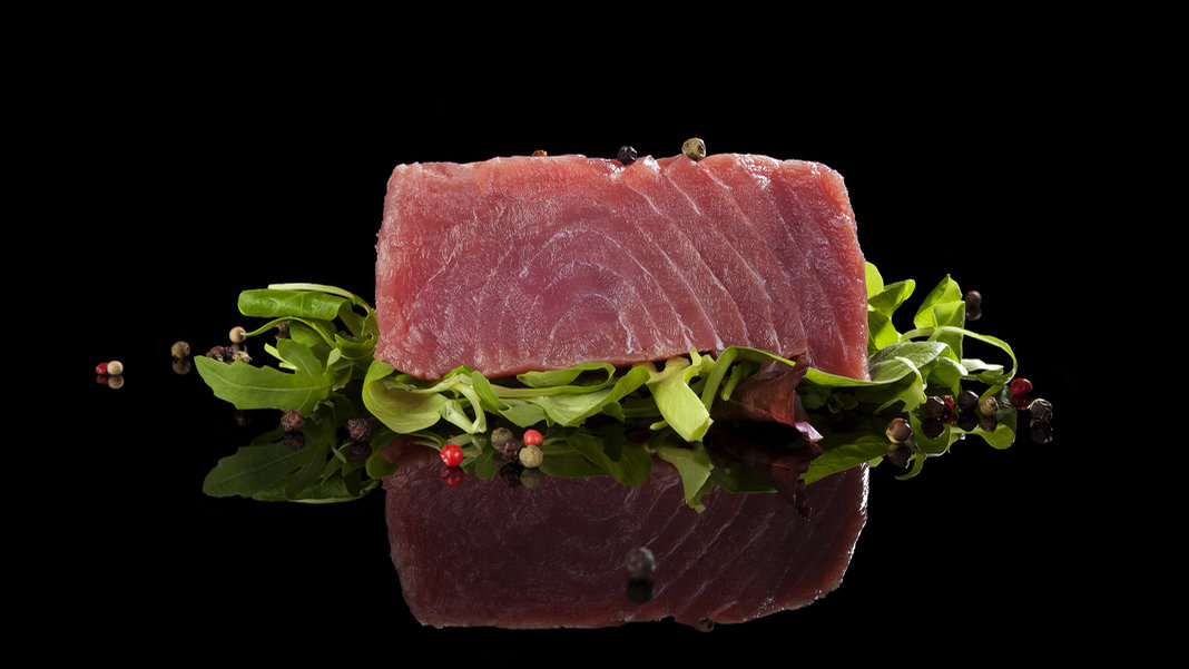 tuna-steak-on-lettuce-black-background-reflection