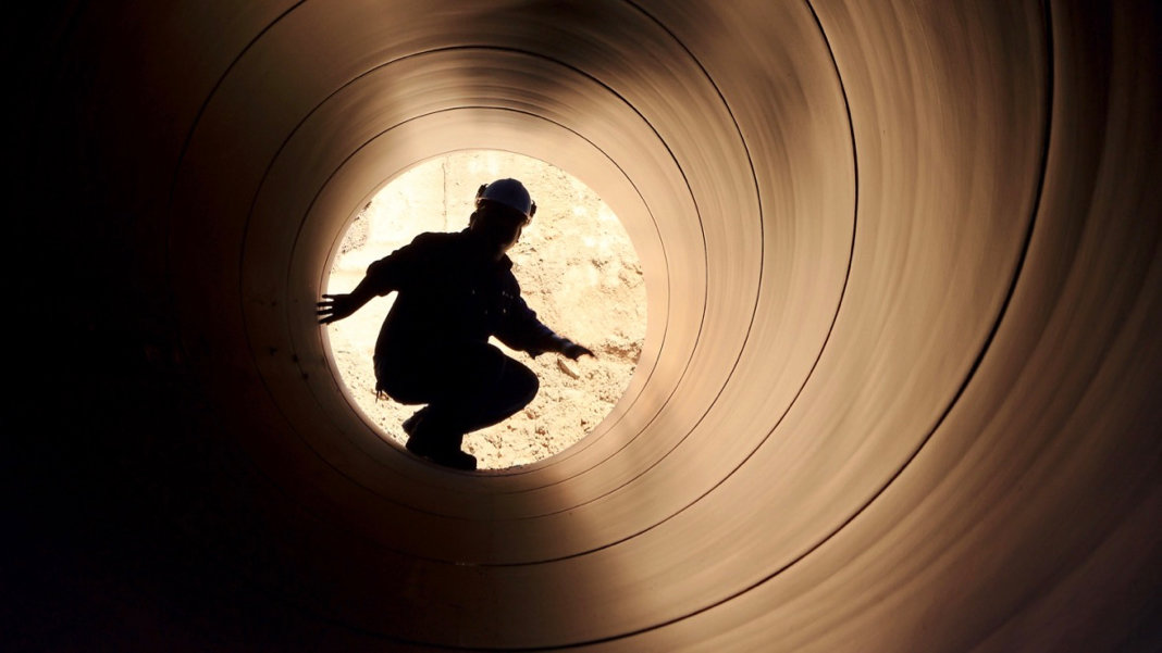 silhouette-of-worker-in-pipe