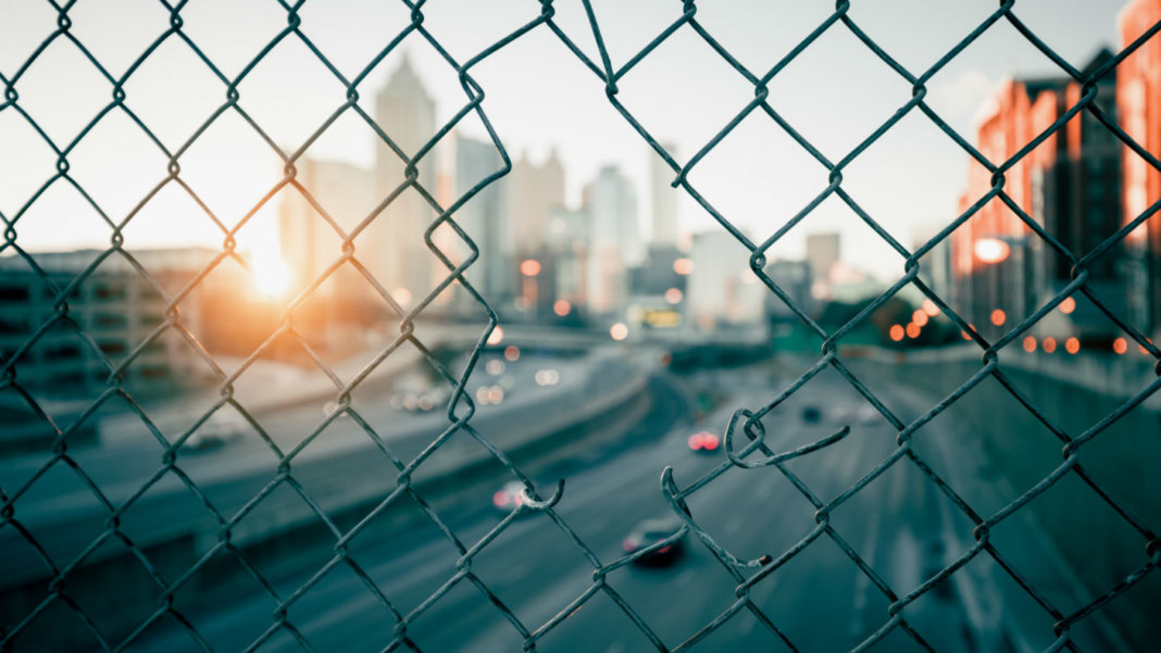 city-sunrise-skyline-through-wire-mesh