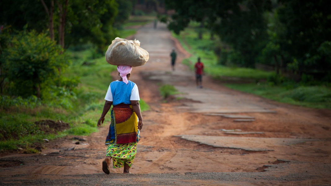 extreme-poverty-free-life-dirt-road-woman-carrying-bundle-on-head