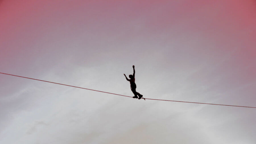 unsafe-thinking-walking-tightrope-slackline-sky-view