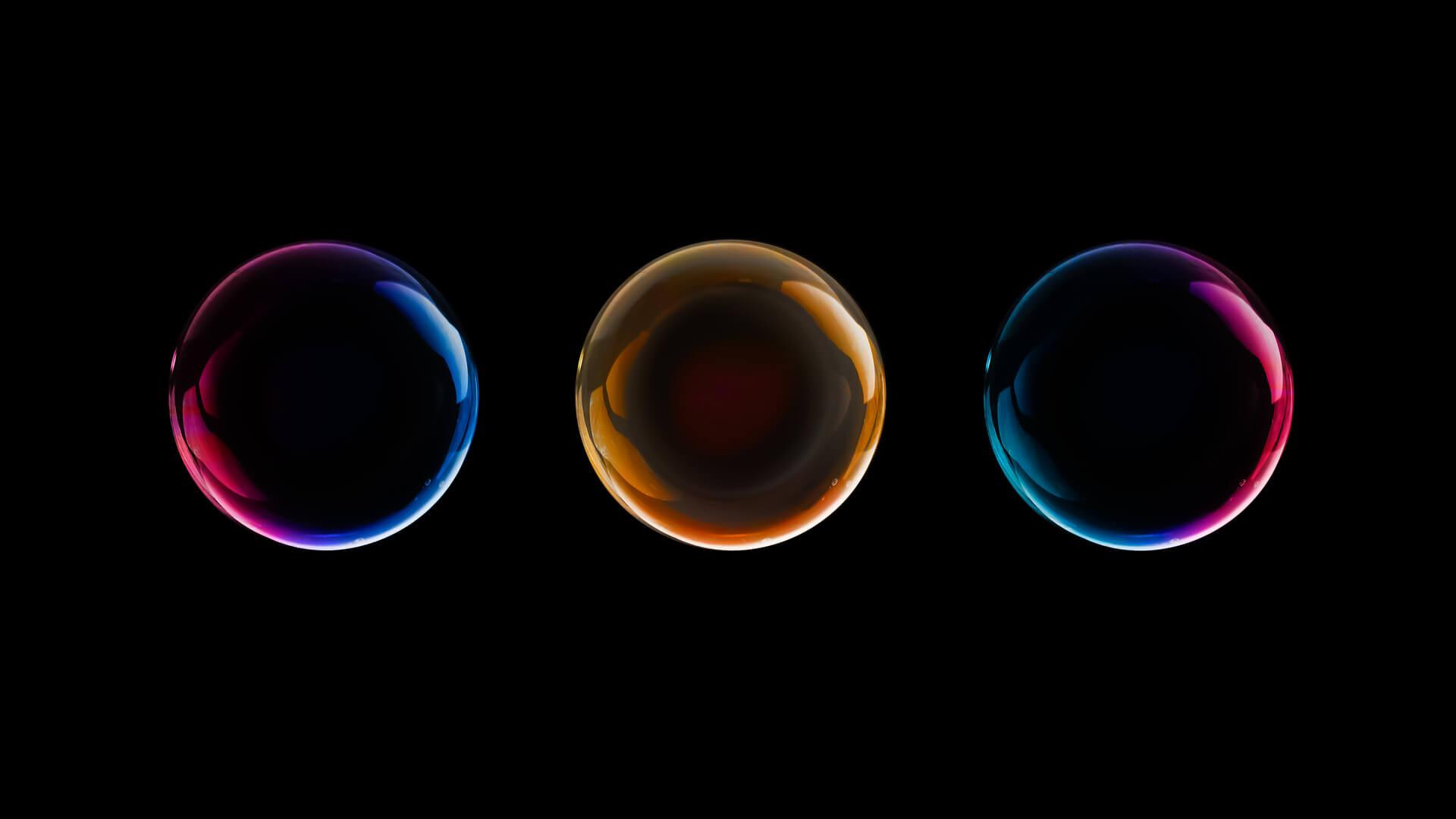 three multicolored bubbles black backround shutterstock 1099317815