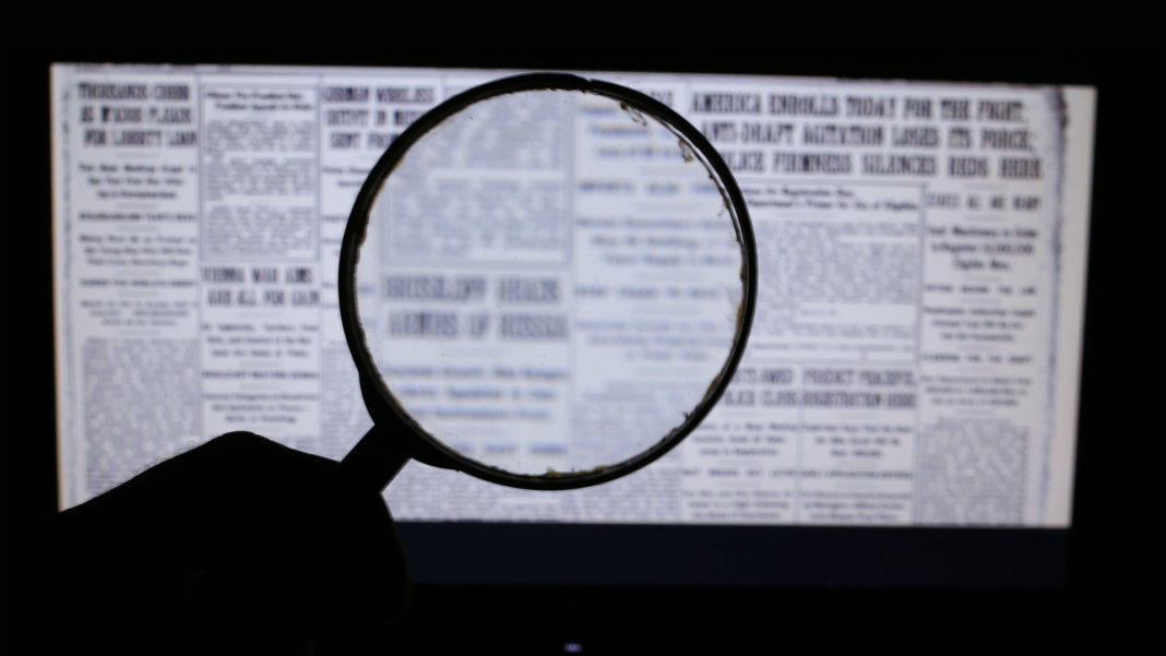 hand holding magnifying glass for fake news on laptop screen artificial intelligence