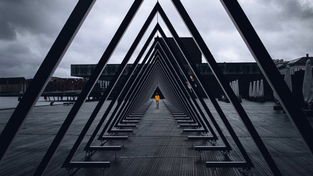 awesome tech stories triangles sculpture vanishing point person orange jacket grey sky
