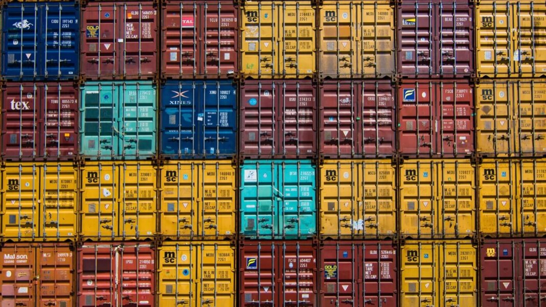 automation supply chain coronavirus stacked shipping containers multicolored