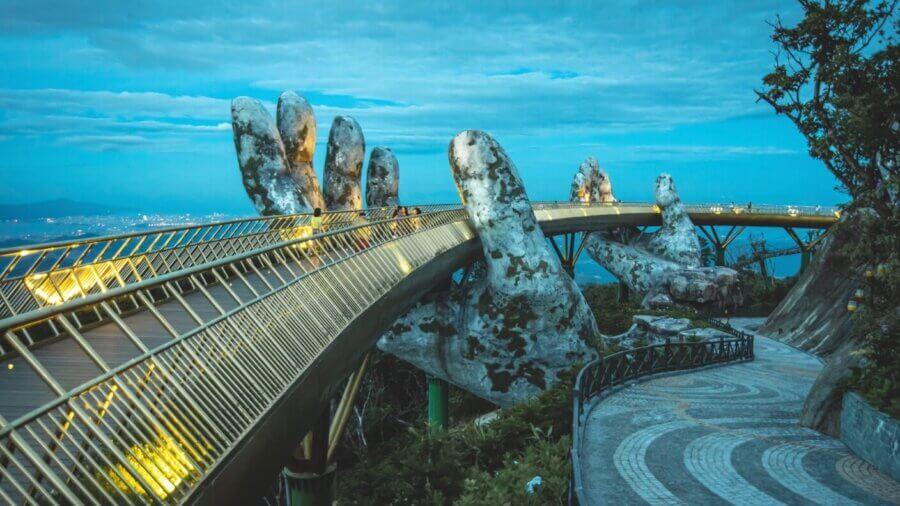 tech stories stone hands golden bridge vietnam dusk trees