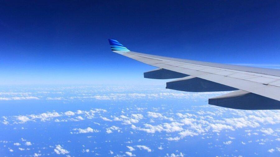 plane wing in blue sky jet fuel emissions